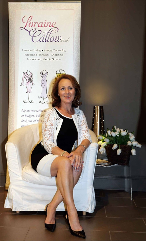 Loraine sitting elegantly in front of her trade banner