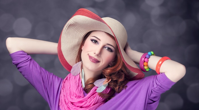 Girl wearing pink and purple, wearing a straw hat